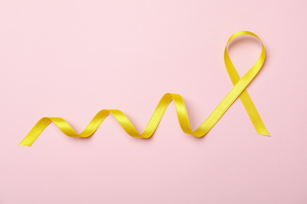 Nastro di consapevolezza giallo su sfondo rosa, spazio per il testo