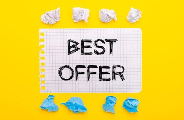 Su uno sfondo giallo, pezzi di carta sgualciti bianchi e blu e un taccuino con il testo migliore offerta.