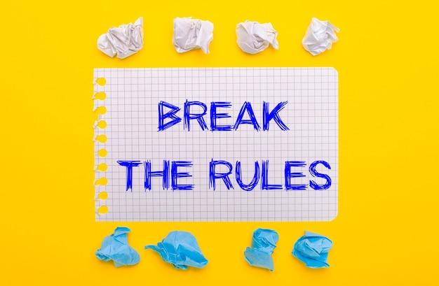 Su uno sfondo giallo, pezzi di carta stropicciati bianchi e blu e un quaderno con il testo break the rules