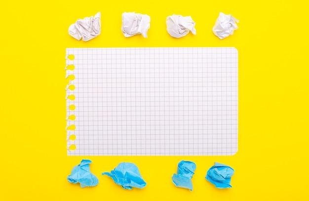 Su uno sfondo giallo, pezzi di carta bianchi e blu e un foglio di quaderno con un posto per inserire del testo. modello