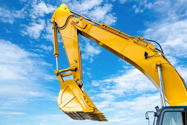 Escavatore a cucchiaia rovescia giallo con il braccio idraulico del pistone contro cielo blu. macchina pesante per scavo in cantiere. macchine idrauliche. enorme bulldozer. industria delle macchine pesanti.
