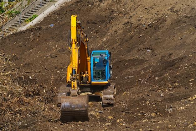 Escavatore a cucchiaia rovescia giallo con braccio a pistone idraulico contro il cielo azzurro. macchina pesante per scavi in cantiere. macchine idrauliche. enorme bulldozer. industria delle macchine pesanti. industria meccanica.