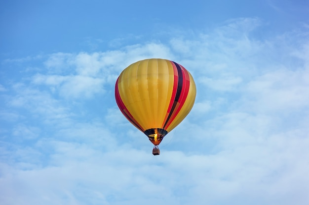 Un pallone giallo sta volando nel cielo un pallone con un cesto giace sull'attrezzatura a terra