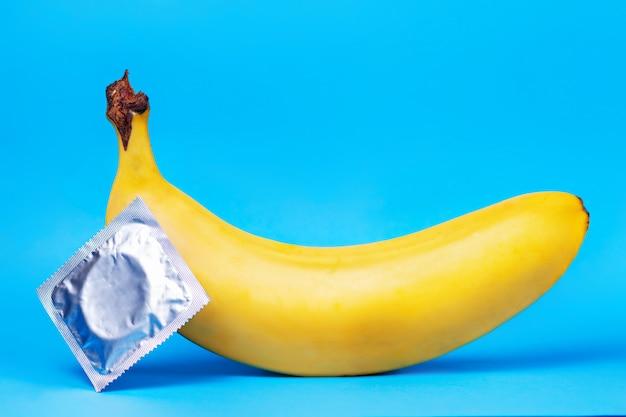 Una banana gialla e un pacchetto di preservativi che si trovano accanto ad esso sul blu
