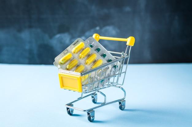 Cestino giallo con pillole su una superficie blu