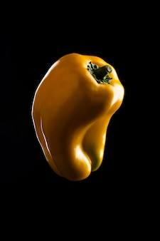 Peperoni dolci gialli accesi sulla superficie nera
