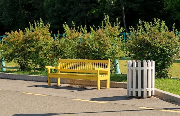 Panchina gialla con cestino in un parco estivo per riposare