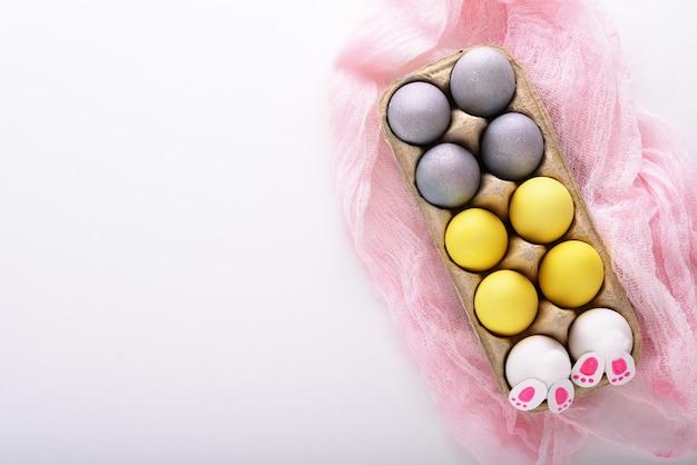 Uova di pasqua gialle e blu, coniglietto di pasqua in scatola di cartone su tessuto rosa su fondo bianco con lo spazio della copia