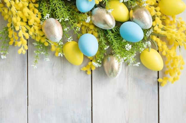 Uova gialle, blu, dorate e rami di mimosa su assi di legno bianchi
