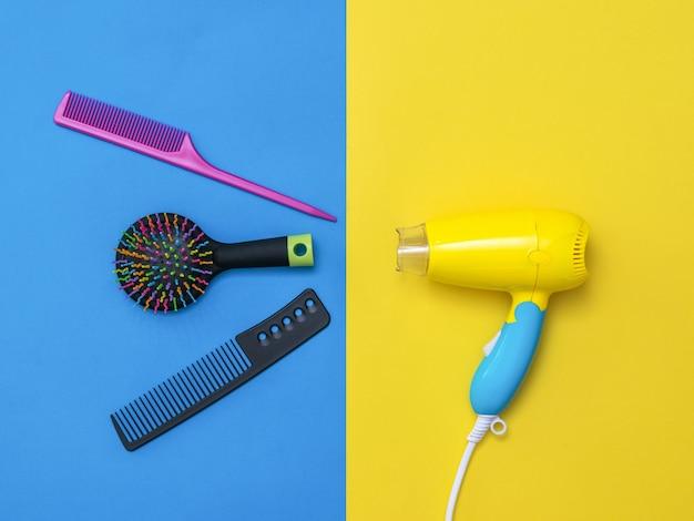 Asciugacapelli giallo-blu con accessori per la cura dei capelli su una superficie colorata