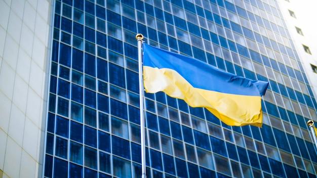 Bandiera ucraina gialla e blu contro il moderno edificio per uffici commerciali