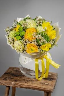 Bouquet giallo di fiori gialli e arancioni su sfondo grigio grigio