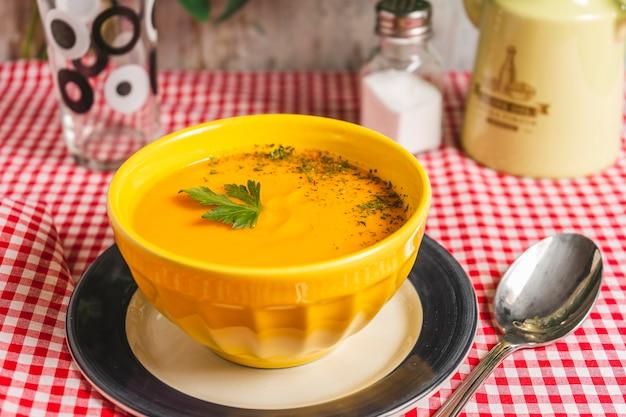 Ciotola gialla con crema di zucca e carote inquadratura orizzontale