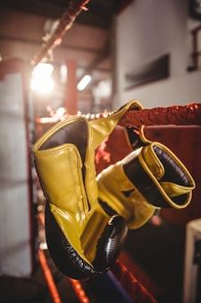 Guantoni da boxe gialli appesi al ring