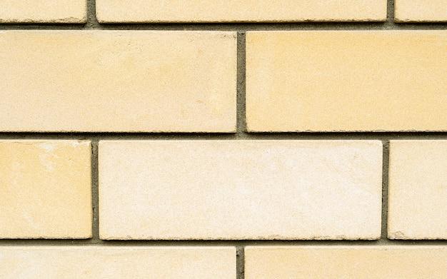 Muro di pietra del mattone giallo come una priorità bassa di struttura, immagine di macro della parete della costruzione di alta risoluzione. la consistenza del muro di pietra. pietra nella sezione. sfondo. ciottoli