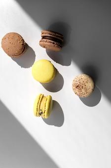 Amaretti francesi di cioccolato giallo e marrone o dessert di macarons su sfondo bianco con raggi di luce dalla finestra.