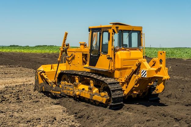 Bulldozer giallo con il trattore cingolato in piedi in un campo