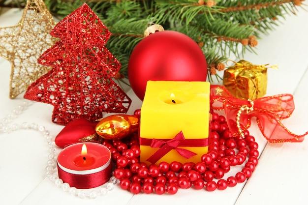 Candela gialla con decorazioni natalizie su superficie chiara