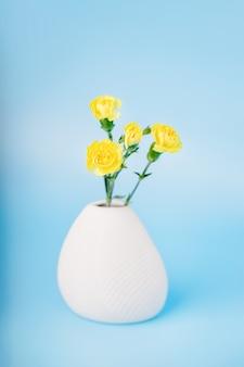 Fiori di garofano giallo in un vaso di ceramica bianca