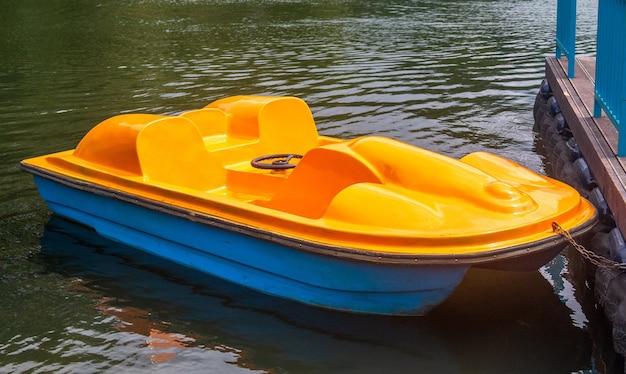 Catamarano giallo a forma di pedalò ormeggiato al molo.