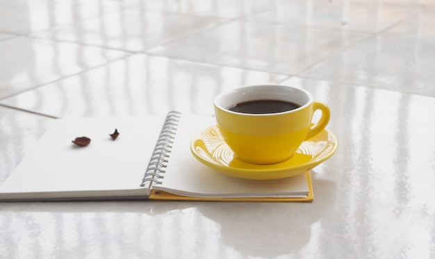 Tazza di ceramica gialla con caffè nero messo su un libro aperto sfocato, luce sfocata intorno