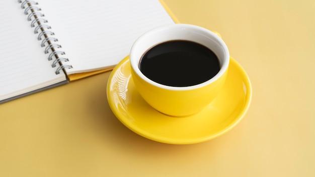 Tazza di ceramica gialla con caffè nero messo davanti a un libro aperto sfocato, su sfondo pastello