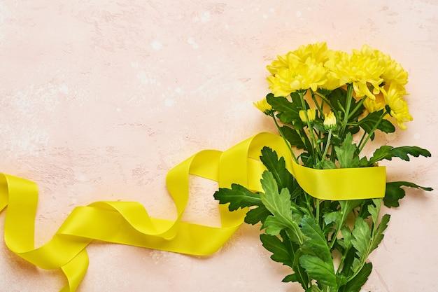 Mazzo di fiori di crisantemi gialli con bellissimo nastro largo su sfondo rosa bnton. modello di biglietto di auguri con copia spazio