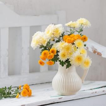 Crisantemi gialli in brocca sulla vecchia panca in legno bianco