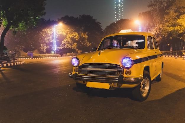 Servizio di taxi classico giallo al parcheggio dell'aeroporto di calcutta di notte. un modello di taxi anni 50-60.