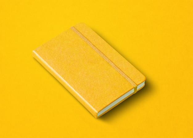 Modello di taccuino chiuso giallo isolato su sfondo colorato