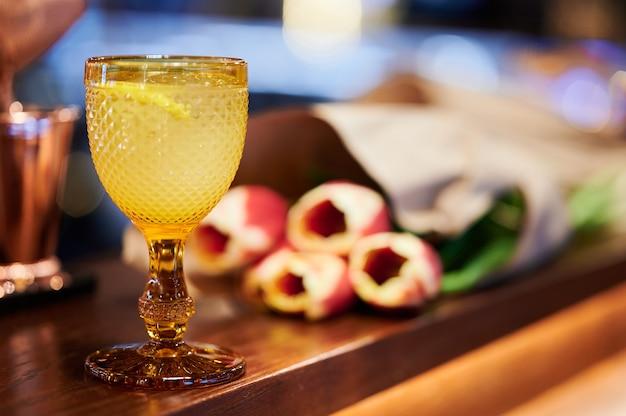 Cocktail giallo con limone e ghiaccio in un bellissimo bicchiere medievale accanto a un bouquet di tulipani giallo-rossi