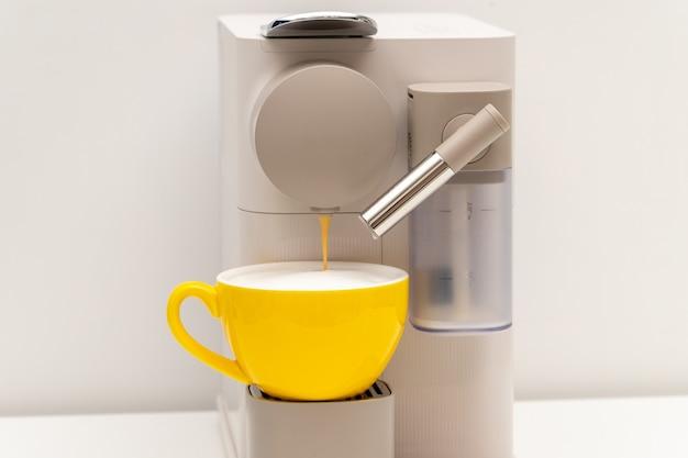 Tazza di caffè gialla e macchina per capsule di caffè