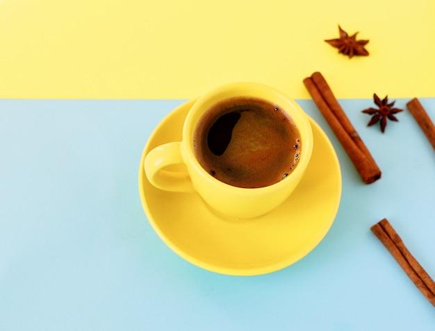 Tazza di caffè gialla su un doppio sfondo giallo e blu con bastoncini di anice e cannella