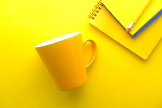Mockup di tazza di colore giallo con quaderni su giallo