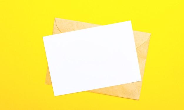 Su una parete di colore giallo, una busta e un biglietto vuoto con spazio per inserire testo o illustrazioni. vista dall'alto con copia spazio