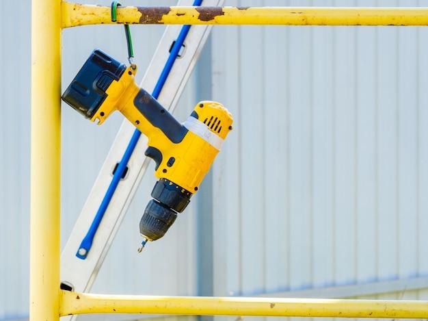 Un cacciavite a batteria giallo è appeso a una barra di impalcatura