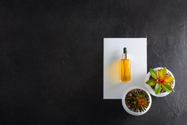 Olio cosmetico giallo su sfondo di pietra nera con piante grasse nel piatto laici