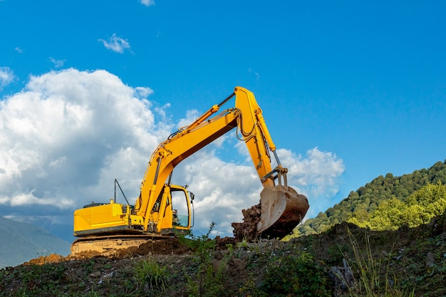 Escavatore cingolato giallo scava il terreno contro il cielo blu con nuvole