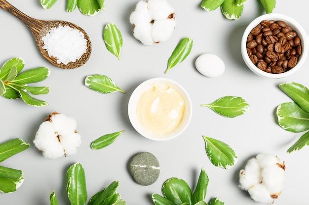 Crema gialla, chicchi di caffè, cotone, sale da bagno e foglie verdi su fondo grigio. cosmetici naturali e concetto di spa. vista dall'alto, piatto.