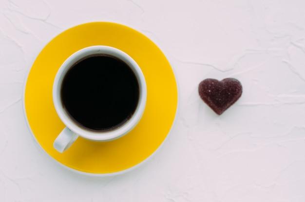 Giallo tazza di caffè e cuore su sfondo bianco. minimalismo. avvicinamento