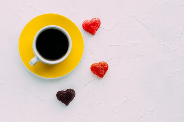 Giallo tazza di caffè e cuore su sfondo bianco. minimalismo. copia spazio