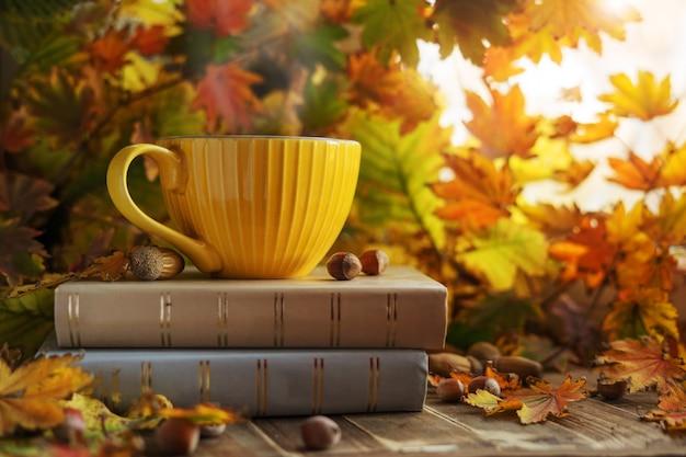 Tazza di caffè gialla su una pila di libri nel fogliame di autunno con ghiande e noci. atmosfera autunnale.