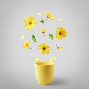 Tazza gialla con fiori gialli volanti su un tavolo grigio. il concetto di primavera.
