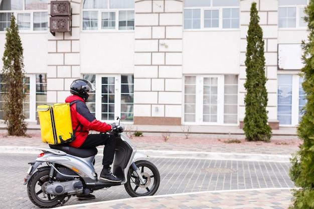 Scatola di consegna gialla sulla motocicletta con fattorino davanti a casa.