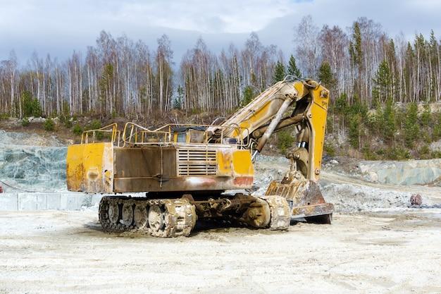L'escavatore sporco giallo sta in una cava per l'estrazione di marmo
