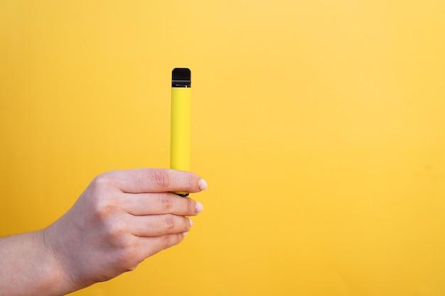 Sigaretta elettronica usa e getta gialla in una mano femminile. sfondo giallo brillante. svapo al gusto di melone, ananas o limone