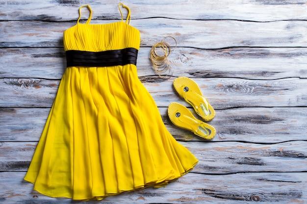 Abito giallo e infradito. abbigliamento casual, calzature e bracciali. luminoso abbigliamento estivo da donna. preparati per la prossima stagione.