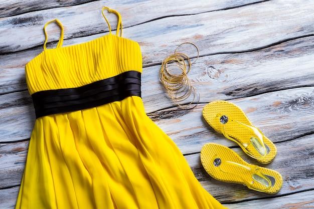 Abito giallo, calzature e bracciali. abito estivo casual e accessori. abbigliamento da ragazza semplice e luminoso. capo luminoso con elemento scuro.