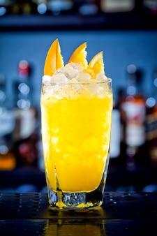 Cocktail giallo con fettine di arancia al bancone del bar.