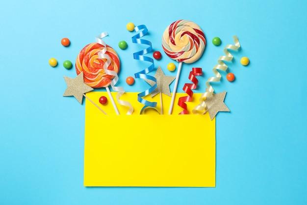 Busta gialla con accessori compleanno su sfondo blu, spazio per il testo